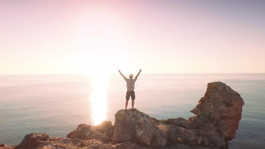 Young Man On Sea Vacation Standing On Edge Of Ocean Cliffs Enjoying Sunrise Happiness Nature Beauty Concept    Shutterstock HD Video #10461932