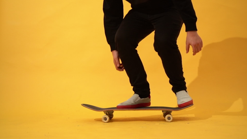 Skateboarder performing skateboard trick in the studio. Athlete practicing stunt jump on yellow background, preparing for competition. Extreme sport, youth culture  | Shutterstock HD Video #1046194216