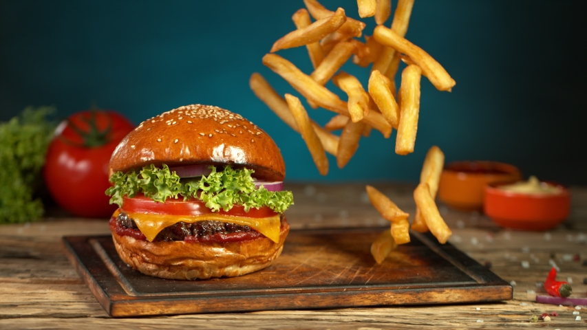 Super Slow Motion Shot of Fast Food Concept. Falling French Fries on Wooden Cutting Board next to the Fresh Hamburger at 1000fps. | Shutterstock HD Video #1046211772