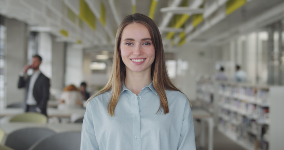 Smiling caucasian girl intern standing at modern office coworking space. Portrait of young female office manager looking to camera and having good mood. Blurred office background. | Shutterstock HD Video #1046223025