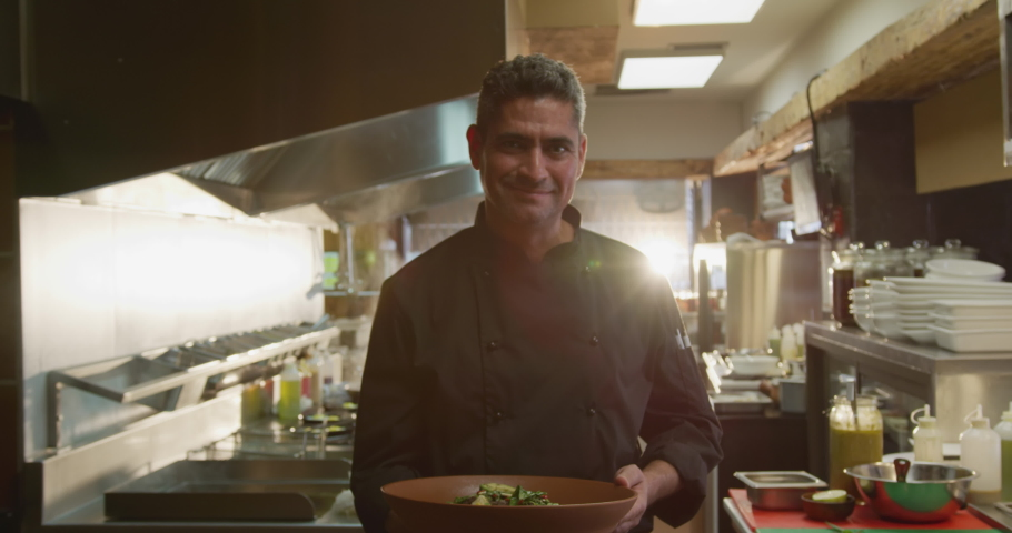 Portrait of a Caucasian male chef working in a busy restaurant kitchen, presenting plate of food to camera, smiling. Busy chefs at work in commercial kitchen.