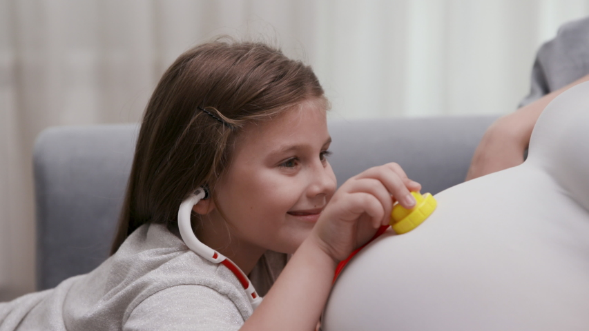 Curious Little Girl Plays at Doctor with Pregnant Female. Adorable Caucasian Daughter Examines a Pregnant Mom Belly with Toy Medical Equipment. Charming Kid and Mother have Fun Hospital Game. Closeup