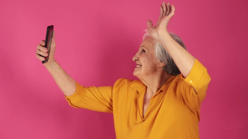 Close up portrait of a very old grandmather makes selfie on phone with say hello, yellow clothes. isolated, pink background
