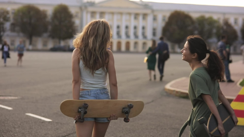 Portrait of two girls Teenage friends with skateboard in sunshine in street european town laughing at something outside and talk. slow motion   Shutterstock HD Video #1046246176
