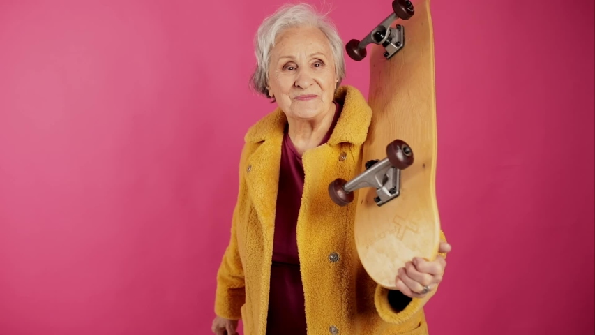Very old grandma, dressed fashionably and youth with a skateboard on the shoulder shows the class hand. isolated, pink background. slow motion