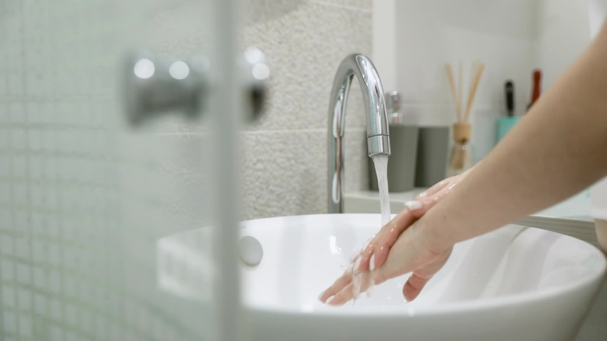 Young people and body care. Person rinsing hands in modern design bathroom at home. Man washing male hand with soap and water under faucet in hotel room during travel. Slow motion | Shutterstock HD Video #1046258479