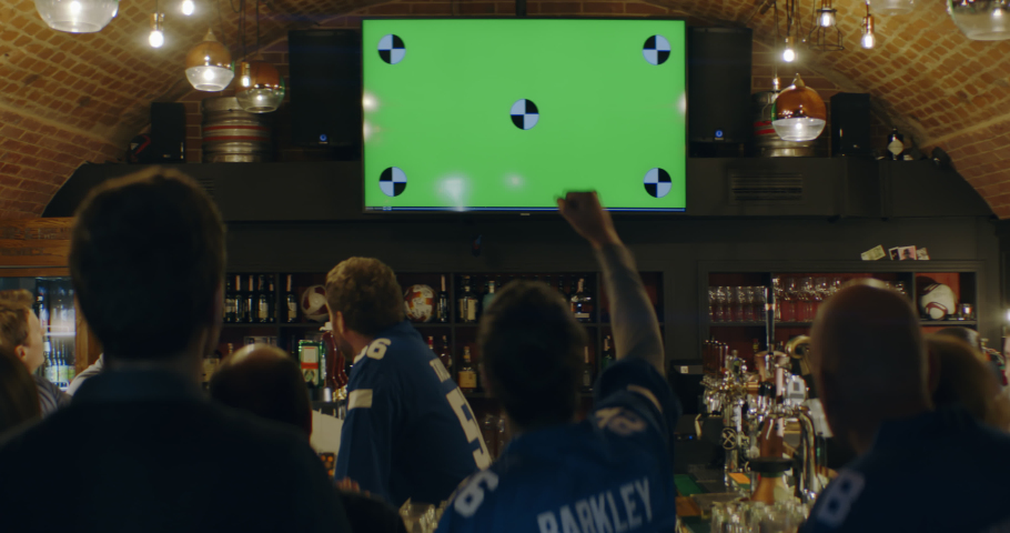 WIDE FIXED Model released, fans watching a game on a large TV in a sport pub, green screen chroma key with tracking points. Shot on ARRI Alexa Mini with Atlas Orion 2x Anamorphic lens