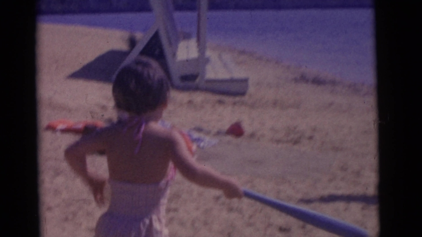 CAMDEN NEW JERSEY USA-1961: Little Girl Swings A Plastic Baseball Bat And Missed The Ball Her Father Throws To Her
