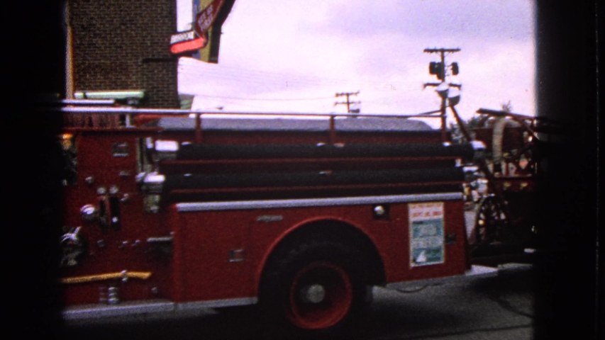 BARRINGTON ILLINOIS USA-1963: Parade Fire Truck And Buggy Turn Corner On A Cloudy Day