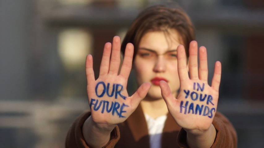 Climat strike, environmental disaster. Close portrait of a beautiful student with an inscription on the palms. Our future in your hands. Young woman protests against global warming