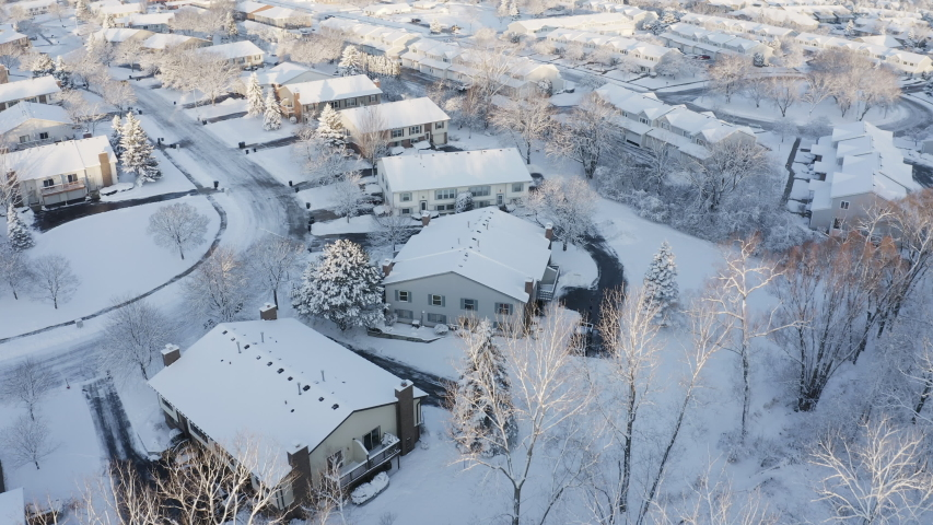 Aerial view of residential houses covered snow at winter season. Establishing shot of american neighborhood, suburb at wintertime.  Real estate, Midwest, sunny morning, soft sunlight. Drone shot