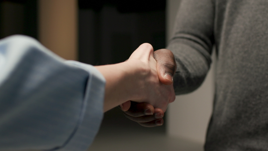 Friendly Handshake African American Man and White Woman. Meeting of Two Business People Indoors. Unrecognizable Multi Ethnic Сouple Person Greeting Each Other. Multicultural Shaking Hands Closeup Shot