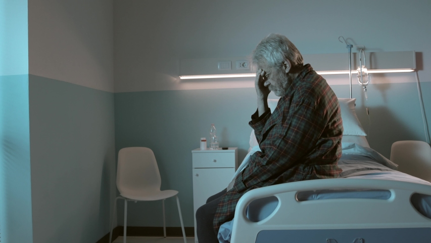 Sad hopeless man sitting in a hospital bed alone at night, he feels depressed and suffers from insomnia