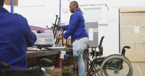 Side view of two African American male workers in a workshop at a factory making wheelchairs, at a workbench assembling parts of a product, one of the workers is disabled and uses a wheelchair to move