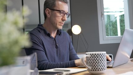 Middle-aged guy having hot drink, working on laptop