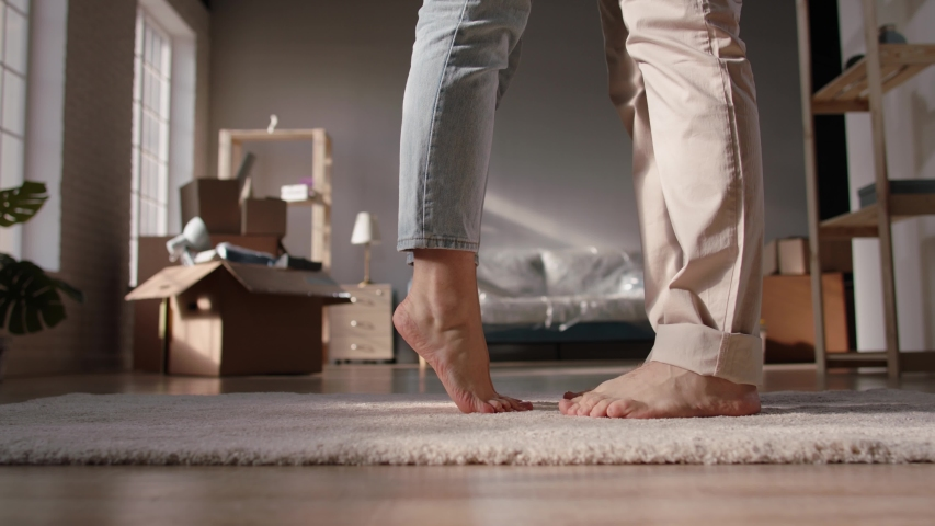 Close-up low angle shot of legs of a cute couple walking barefoot on floor of their new home. Girl standing on tip-toes to kiss her boyfriend - love, new life concept 4k footage