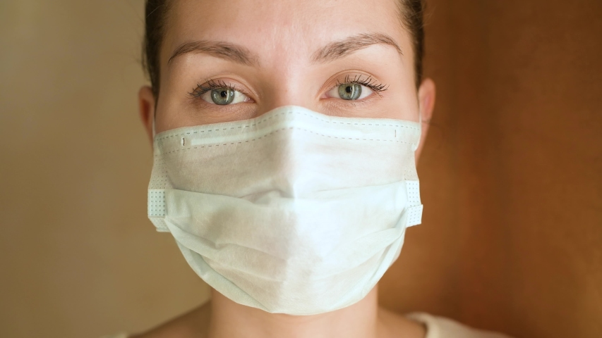 Close-up of a young woman in a protective medical mask, she looks directly at the camera and then turns to the window | Shutterstock HD Video #1046327917