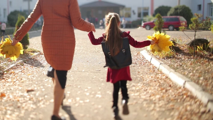 Mother and a little girl in red dress with a backpack on shoulders and a bouquet of yellow autumn leaves in hand go to school. Sunny autumn. 4K video. Royalty-Free Stock Footage #1046337373