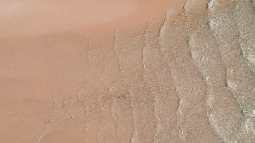 Waves of water gently rolling over pristine sands. Abstract. Overhead shot.  | Shutterstock HD Video #1046338780