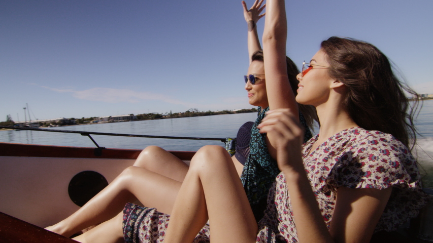 Two beautiful young women having fun, cruising in a wooden motorboat, putting their hands up, laughing, wind in their hair. Medium to long shot on 4K RED camera with lens flare.