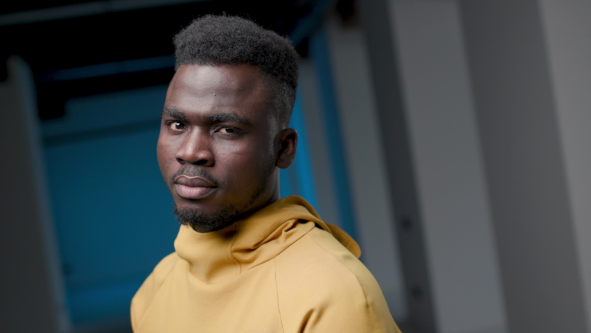 Serious Angry African Man Standing Indoors. Portrait Young African American 30s Man Looking at Camera and Upset Stress. Closeup Face Sad Pensive Man. Contemporary Urban Person Fury. Black Lives Matter | Shutterstock HD Video #1046376976
