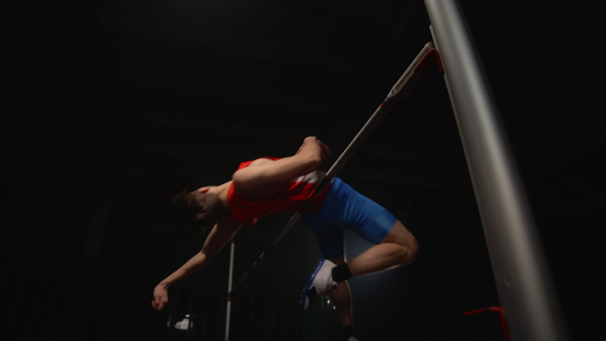 A male athlete runs and jumps high over the crossbar. Slow-motion shooting of the high jump competition. Professional Olympic sports Royalty-Free Stock Footage #1046380819