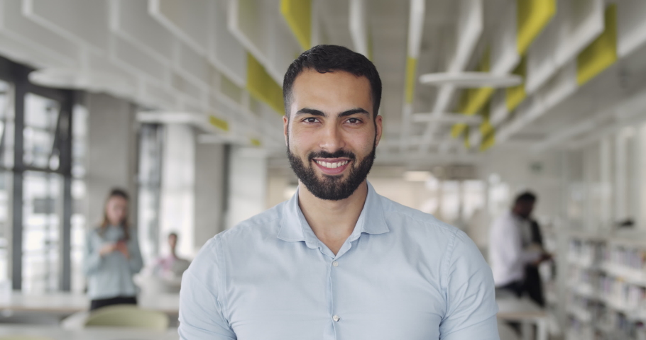 Front view of it trainee looking to camera and smiling at coworking zone. Young startup founder looking happy and standing at office room.Portraits. Concept of work , business, it industry. Royalty-Free Stock Footage #1046385172