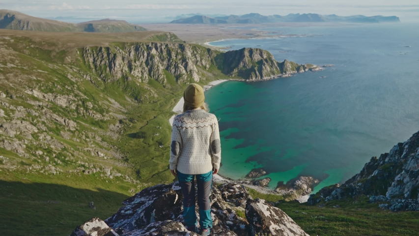 Woman standing alone on mountain top raised hands above ocean travel in Norway adventure vacations healthy lifestyle explore summer activity landscape rocks and sea aerial view   Shutterstock HD Video #1046394352