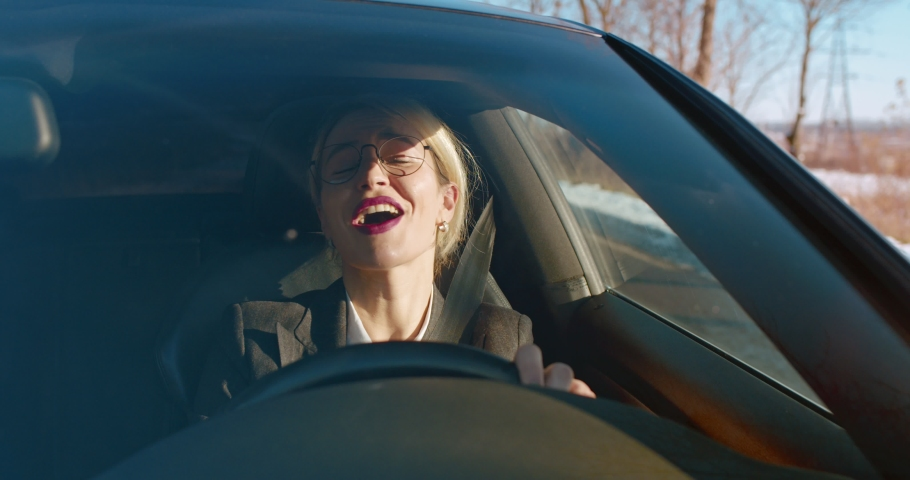 Cheerful and attractive woman in glasses and business style driving a car and singing while listening to the radio on the way to work.