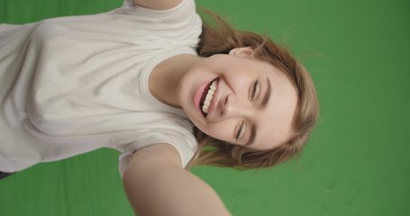 Young smiling hipster blond woman in white t-shirt posing over green screen background. Girl taking selfie self portrait photos on smartphone. Vertical 4k raw video footage slow motion 60 fps