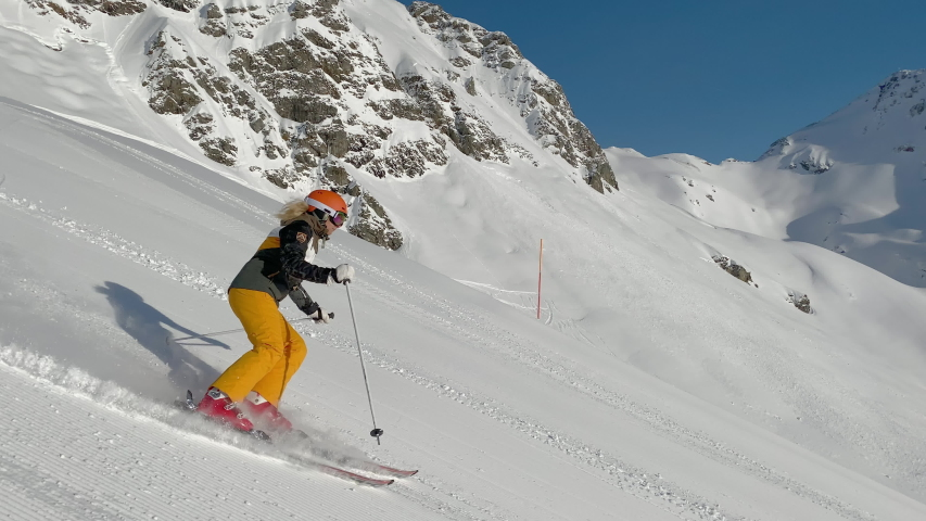 4K skiing footage, one woman skilled skier skiing on ski slope in long turns carving on sunny winter vacation day during ski holidays with clear blue sky high up in european alps mountains