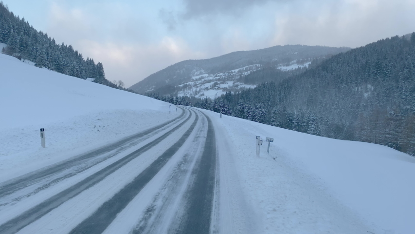4K travel footage, driving on country road covered with snow through rural mountain forest landscape in winter on way to ski holidays in austria europe  | Shutterstock HD Video #1046399389