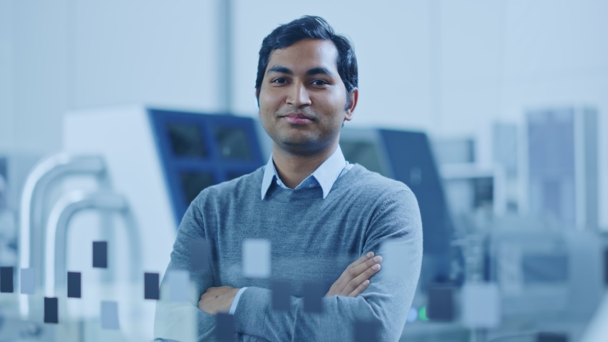 Modern Factory Office: Portrait of Handsome Indian Engineer Crosses Arms and Smiles Charmingly. In the Background High Tech Facility with CNC Machinery, Robot Arm and People Working Royalty-Free Stock Footage #1046400682