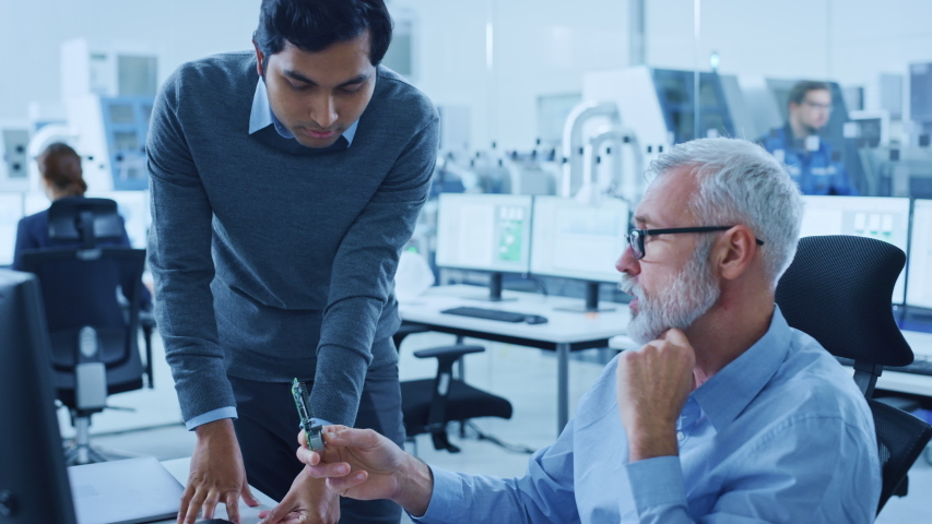 Modern Factory Office: Indian Project Manager Talks to Caucasian Senior Engineer who Working on Computer, Inspect Metal Component. Professionals Solving Heavy Industry Problems, Having Discussion Royalty-Free Stock Footage #1046400751