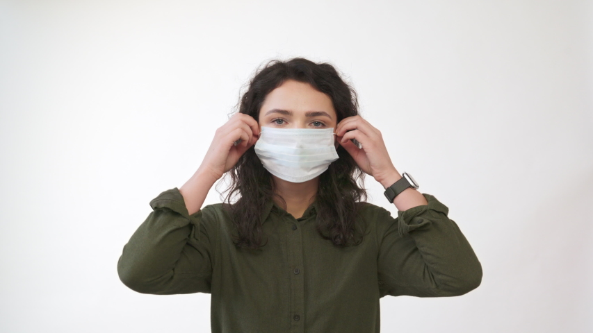 Young woman takes off medical mask. Female breathes deeply and smiling looking at camera. Isolated on white  background. Health care and medical concept. Close up portrait . 4k