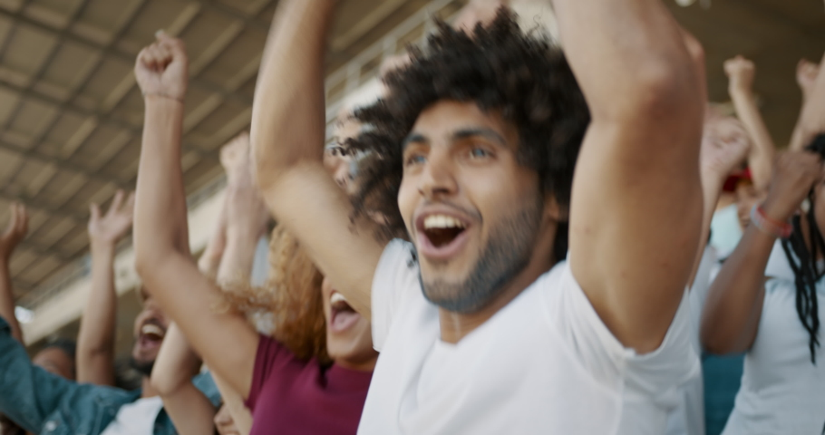 Young couple watching a sport event, jumping with hands raised, giving each other high five and hugging. Excited crowd of sports fans applauding and celebrating their team's victory.  | Shutterstock HD Video #1046414524