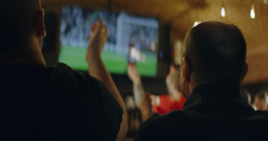 HANDHELD Model released, fans watching a game on a large TV in a sport pub. Shot on ARRI Alexa Mini with Atlas Orion 2x Anamorphic lens | Shutterstock HD Video #1046417368