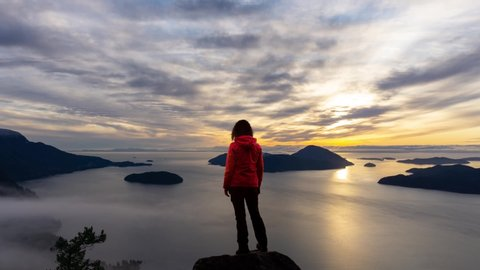 Time Lapse. Adventure Female Hiker on top of a high rocky mountain peak during a vibrant winter sunset. Composite Image Animation. Taken in Howe Sound near Vancouver, British Columbia, Canada.