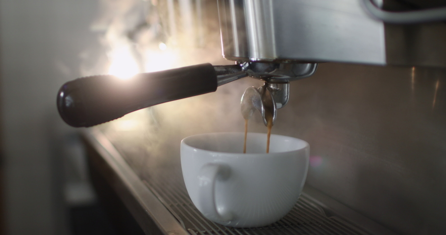 Making a cup of strong coffee in a coffee machine, the back light illuminates the steam and the cup. Royalty-Free Stock Footage #1046431882