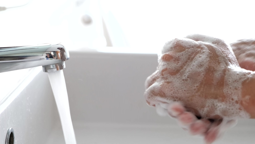 Hands of woman wash their hands in a sink with foam to wash the skin and water flows through the hands. Concept of health, cleaning and preventing germs and coronavirus from contacting hands