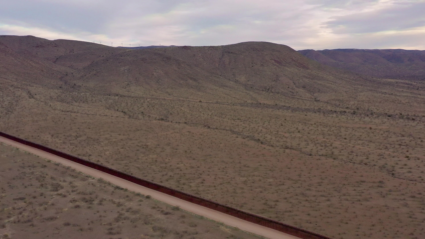 Aerial drone flying along the United States Mexico border fence, showing gap