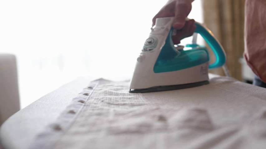 Male hands ironing clothes with iron on ironing board. slow motion