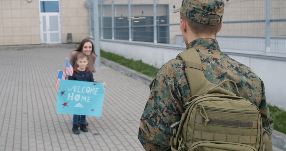 Beautiful wife and son with meeting military man outdoors. Happy little kid throwing welcome home poster and running to his military father. Family of soldier in embrace. Concept of reunion