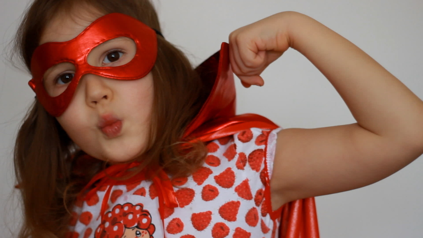 Cute baby girl plays superhero. Funny child in a red raincoat and mask playing power super hero. Superhero and power concept. Portrait close up