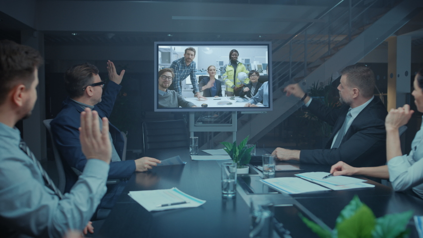 Late at Night Diverse Group of Executives and Management in the Meeting Room, Have Conference Video Call with Team of Engineers, Production Line Specialists. Optimizing Company Production and Growth Royalty-Free Stock Footage #1046470915