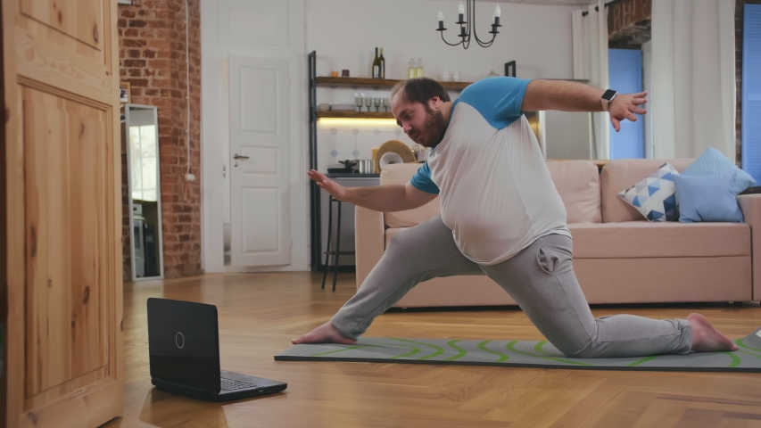 fat man doing gymnastics for losing weight at home on mat on floor watching tutorial video on laptop. Overweight guy doing yoga exercises at home. #1046488777