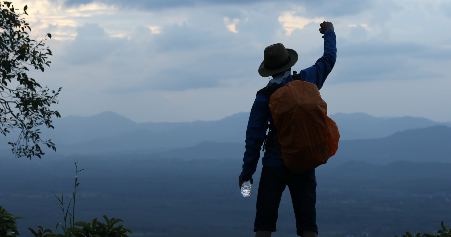 Backpacker drinking water, Tourists Raise your fist above your head enjoying the nature, the mountain with nature during sunset  Royalty-Free Stock Footage #1046501614