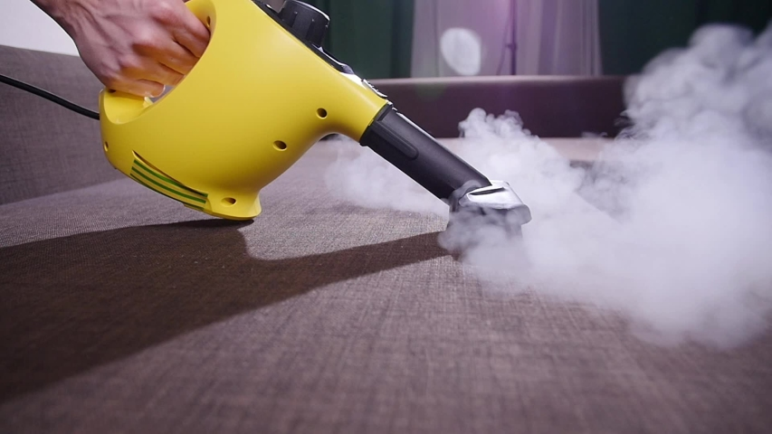 Furniture and apartment cleaning concept. Man cleaning couch with steam cleaner at home | Shutterstock HD Video #1046512897