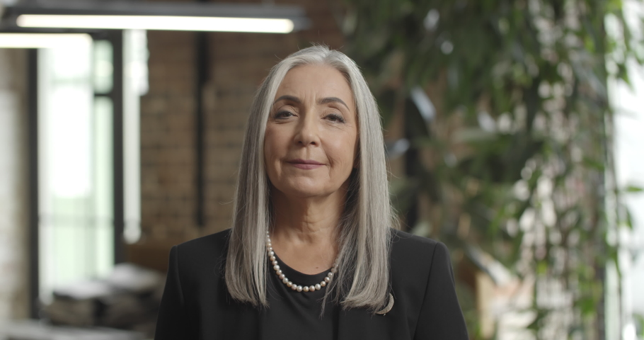 Close up of old elegant businesswoman standing and crossing hands. Independent woman in 50s ceo executive looking to camera, posing and smiling. Portraits. Blurred office background.