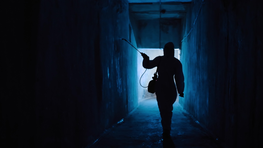 Silhouette of man in protective suit in dark tunnel sprays disinfectant liquid on walls. Virologist in hazmat disinfects room from bacteria and diseases, coronavirus prevention, epidemic, USA, Italy